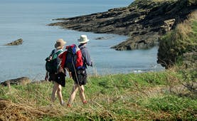 Couple walking on coastal path overlooking sea and cliffs Northumberland