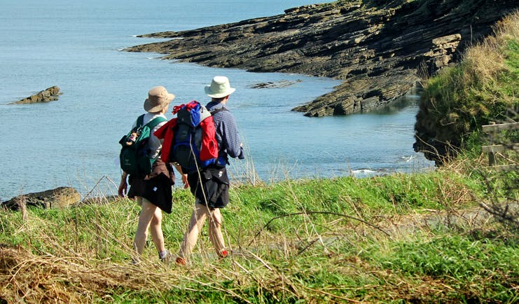 Couple walking on coastal path overlooking sea and cliffs Northumberland