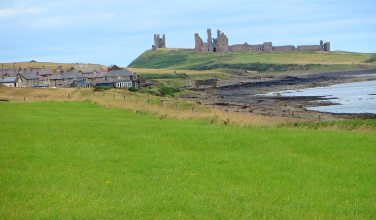 Ruins of castle on hill by sea Northumberland