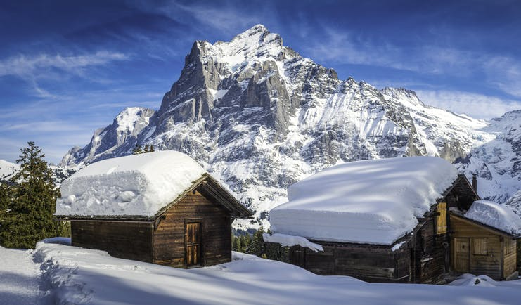 Alpine wooden houses with thick snow on roof at Grindelwald