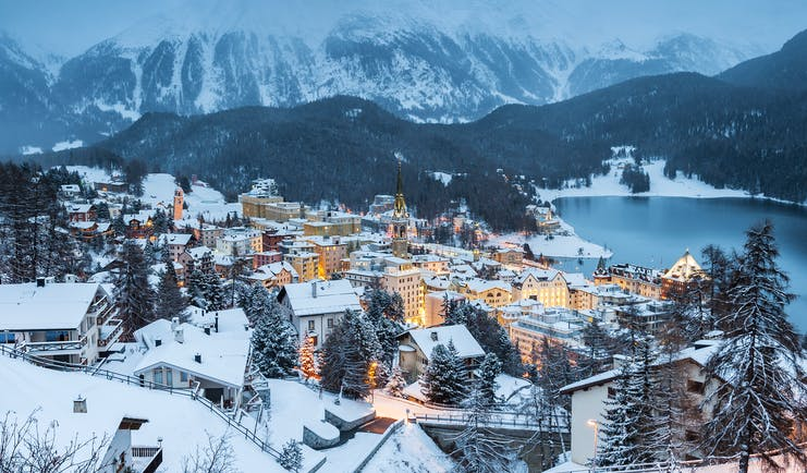 Dusk winter view of St Moritz town, lake and mountains