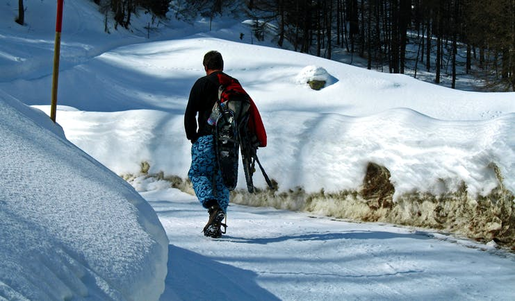 Man walking in winter on snowy track carrying snowshoes
