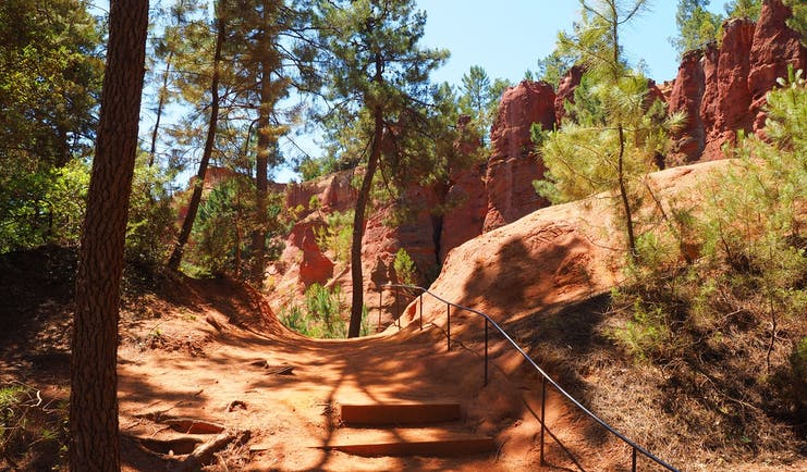 Path on red soil with trees and cliffs