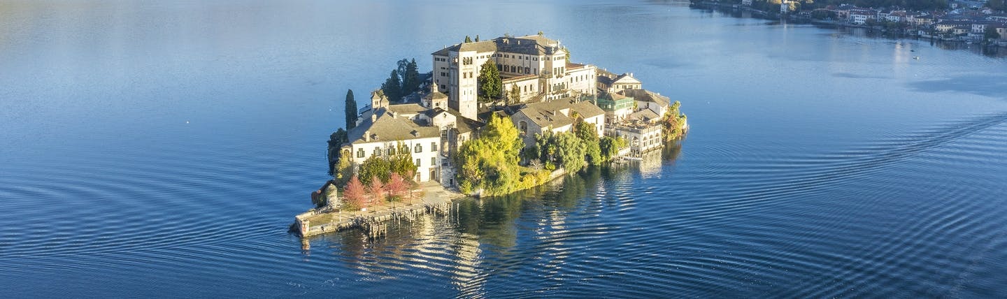 Small island with a few houses on it in the middle of blue lake Orta