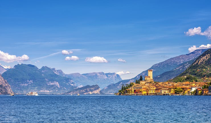 Orange coloured town of Malcesine perched on shore of blue waters of Lake garda with mountains