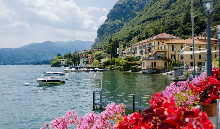 Red and pink geraniums on side of lake with small boats and the village of Menaggio on Lake Como