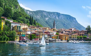 Sailing boat on deep blue water of lake como with town of Varenna on the shore