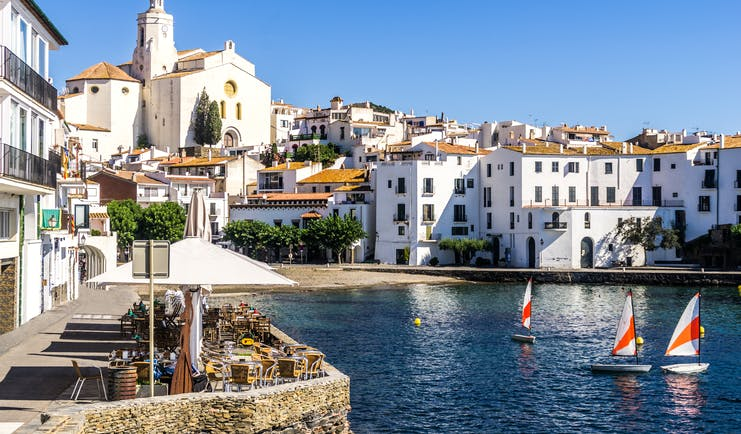 Harbour with small sail boats and white houses lining the seafront, cafe on one side, in Costa Brava town of Cadaques
